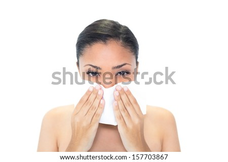 Sad young dark haired woman sneezing in a tissue on white background
