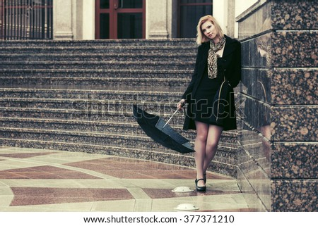 Sad young fashion woman in black coat with umbrella at the wall - stock photo