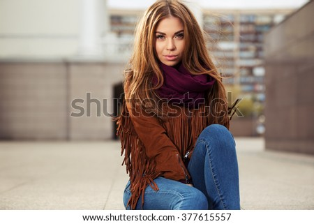 Sad young fashion woman in leather jacket on city street
