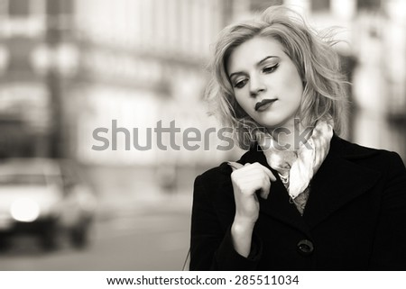 Sad young fashion woman walking on a city street