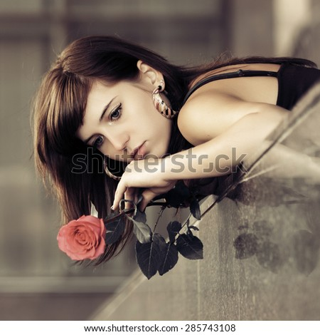 Sad young fashion woman with a red rose outdoor - stock photo