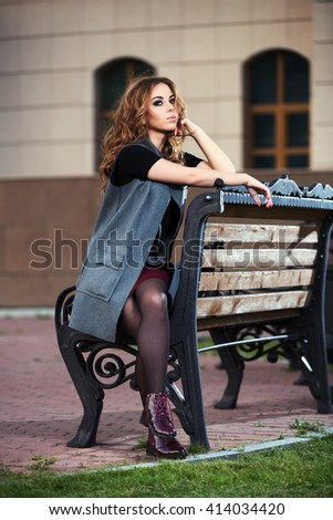 Sad young fashion woman with long curly hairs sitting on bench. Female stylish model in grey coat outdoor - stock photo