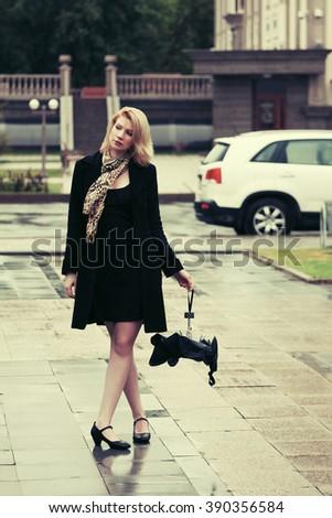 Sad young fashion woman with umbrella walking on city street - stock photo