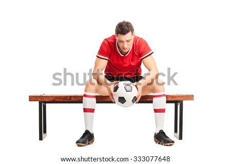 Sad young football player sitting on a wooden bench and looking down isolated on white background - stock photo