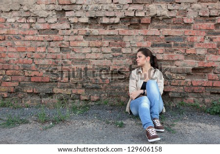 Sad young girl sitting against a brick wall - stock photo