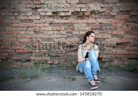 Sad young girl sitting against a brick wall