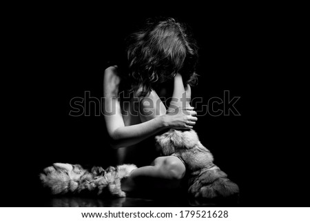 Sad young girl sitting on carpet - black and white photo - stock photo