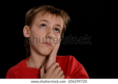 sad young guy in the red shirt on a black background - stock photo