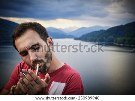 Sad young handsome man smokes a cigarette in the park. - stock photo