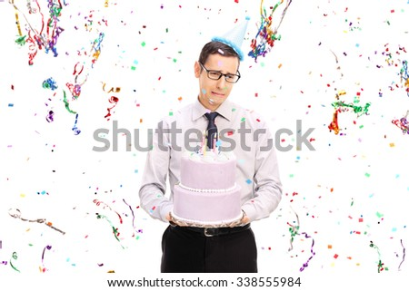 Sad young man holding a birthday cake and crying with confetti streamers flying around him isolated on white background