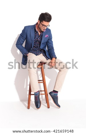 sad young man in suit sitting and looking down in studio - stock photo