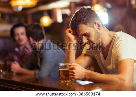 Sad young man in white t-shirt is looking at glass of beer while sitting at bar counter in pub, in the background two other men - stock photo