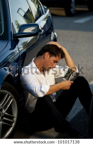 Sad Young Man looking at his girlfriend/wife picture. Concept: end of love, separation. - stock photo