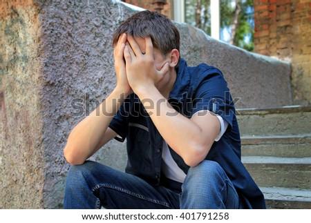 Sad Young Man sit on the City Street - stock photo