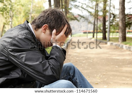 sad young man sitting in the autumn park - stock photo