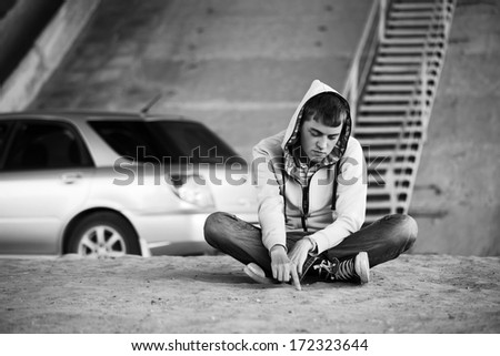 Sad young man sitting on the ground - stock photo