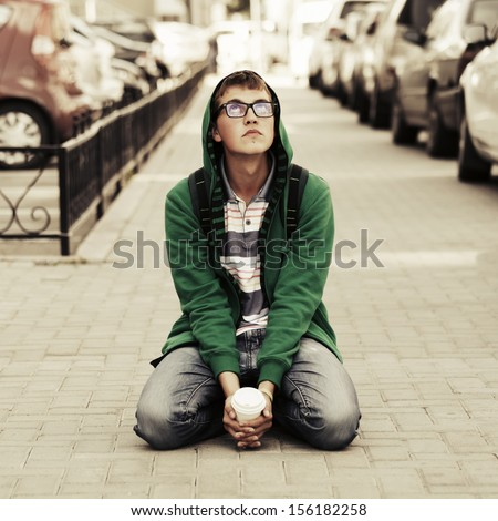 Sad young man sitting on the sidewalk against a city traffic - stock photo