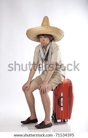 Sad young mexican man sitting on his luggage being disappointed or confused.