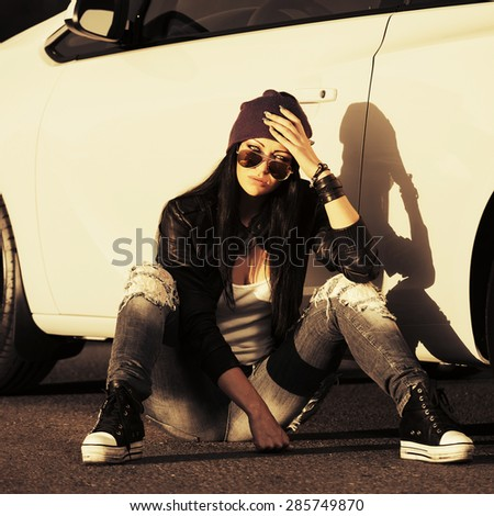Sad young stylish fashion woman in sunglasses sitting by her car outdoor - stock photo