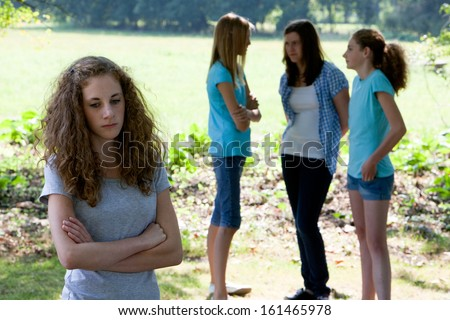 Sad young teenage girl standing with folded arms as her teenage peers ignore her and stand in a group chatting , conceptual of a social outcast