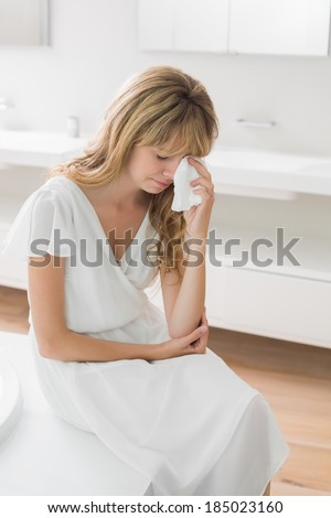 Sad young woman crying in the bathroom at home - stock photo