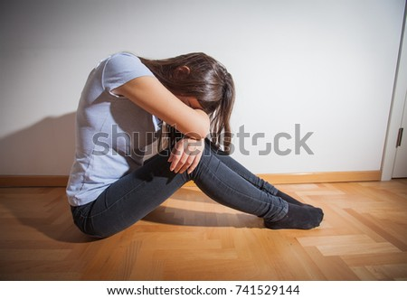 Sad young woman , depressed female , emotional problems, sitting on floor at empty room.