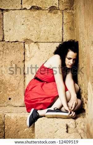 Sad young woman in a corner