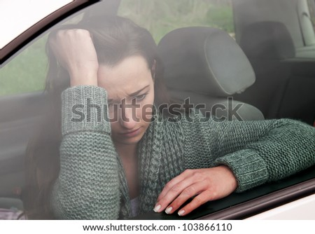 sad young woman in the car - stock photo