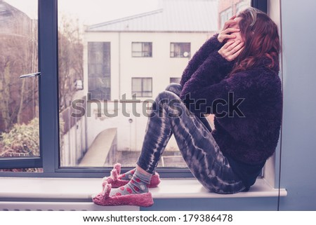 Sad young woman is sitting by the window - stock photo
