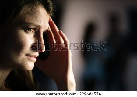 Sad young woman is suffering after breakup while  having flashbacks with her boyfriend - couple silhouettes on the background - stock photo
