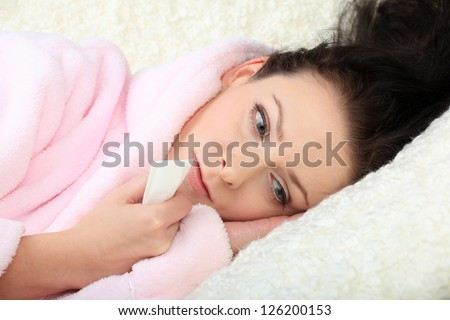 Sad young woman lies on a sofa and holds a tissue in a hand