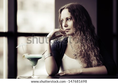 Sad young woman looking out the window - stock photo