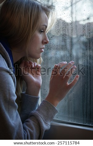 sad young woman looking through window with raindrops