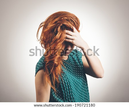Sad Young Woman Looks Down And Covers Eyes - stock photo