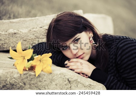 Sad young woman lying on the tombstone  - stock photo