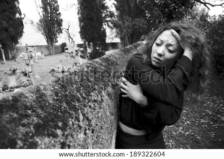 Sad young woman. She is really depressed. She wears black clothes. She stands along the wall of a cemetery. Her pain is very hard. - stock photo