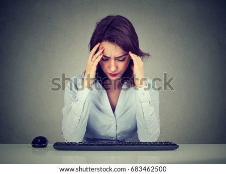 Sad young woman sitting at table looking down at computer keyboard