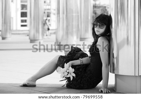 Sad young woman sitting on a sidewalk