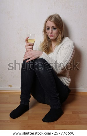 sad young woman sitting on the floor with wine glass crying                         - stock photo