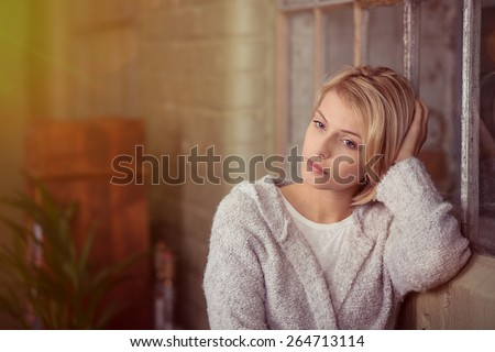 Sad young woman sitting thinking resting her head on her hand on the back of the sofa as she stares at the ground with a serious expression - stock photo