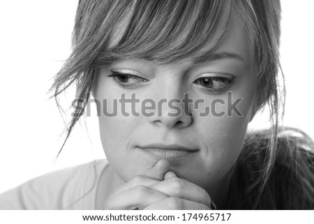 Sad Young Woman - This is a close up black and white portrait of a sad young woman struggling to make a decision. Shot with a shallow depth of field on a white background.