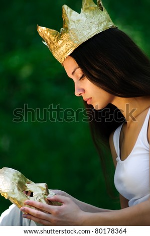 Sad young woman wearing crown looking at gold mask