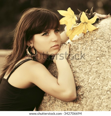 Sad young woman with a flowers daydreaming outdoor - stock photo