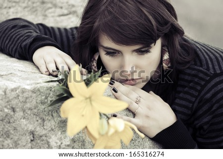 Sad young woman with a flowers lying on the tombstone - stock photo