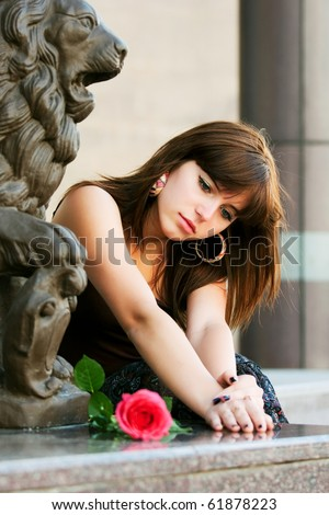Sad young woman with a rose. - stock photo