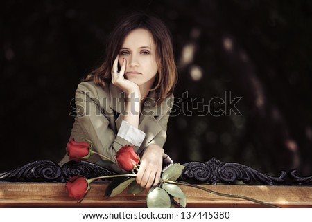 Sad young woman with a roses - stock photo