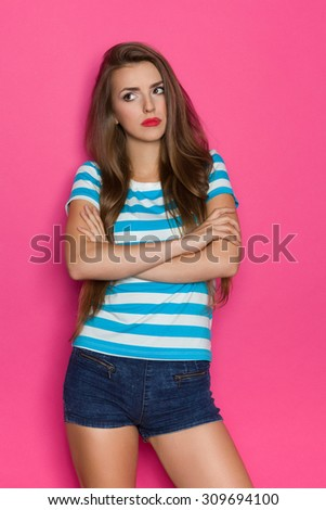 Sad Young Woman With Arms Crossed. Grimacing girl in striped shirt and jeans shorts posing with arms crossed and looking away. Three quarter length studio shot on pink background. - stock photo