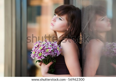 Sad young woman with chrysanthemum. - stock photo