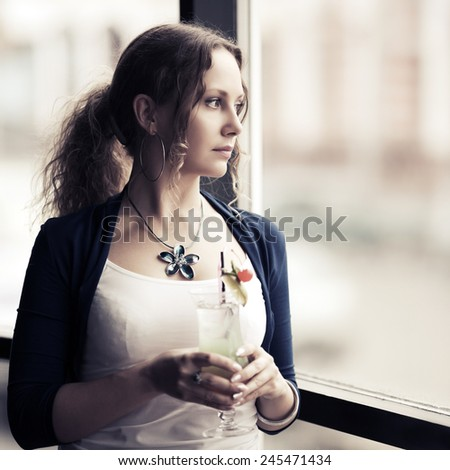 Sad young woman with cocktail looking out window  - stock photo