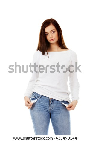 Sad young woman with empty pockets - stock photo